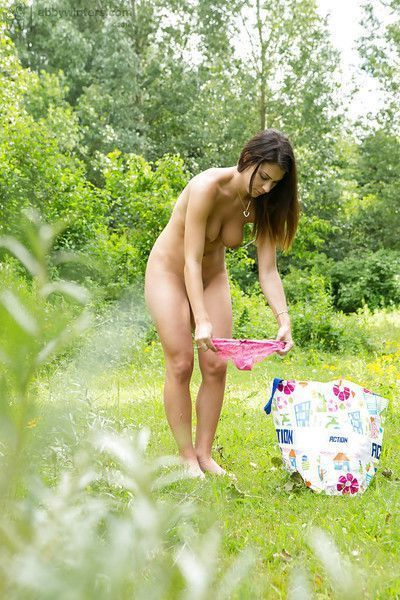 Amateur model Amelia B pulling panties over bare ass outdoors in woods