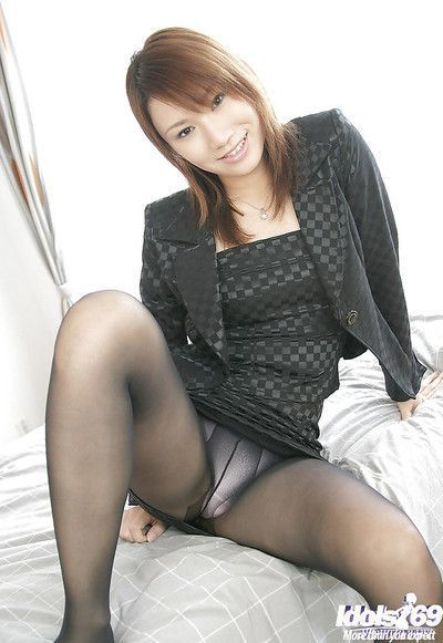 Tempting asian babe in nylon pantyhose stripping on the bed