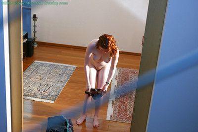 Hidden camera captures all natural redhead pulling panties over nice ass