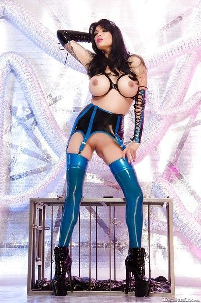 Buxom fetish model hitting hot poses in latex leggings and garters