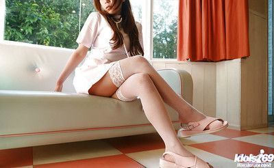 Seductive asian babe with big jugs stripping off her nurse uniform