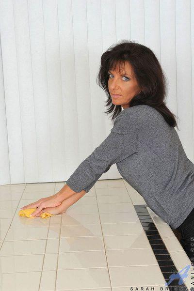 Mature woman Sarah Bricks baring big tits before sliding pantyhose over ass